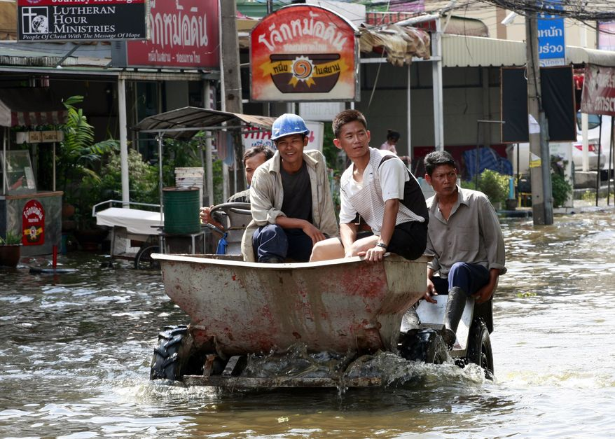 Workers ride on their vehicle through a flooded road in Bangkok, Thailand, Saturday, Oct. 22, 2011. Thailand's catastrophic floods may take up to six weeks to recede, Prime Minister Yingluck Shinawatra said Saturday. (AP Photo/Apichart Weerawong)