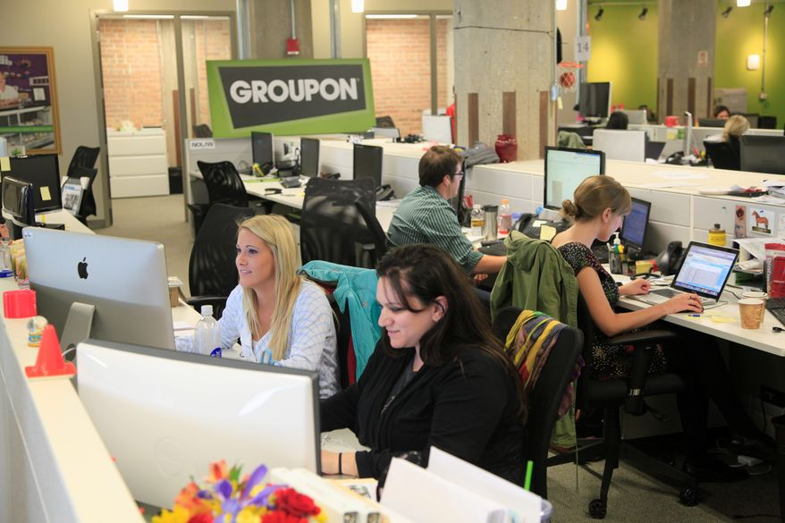 Groupon employees Amanda Allegretti (left) and Becca Silvers work at the online-coupon company's offices Sept. 22 in Chicago. Online-coupon seller Groupon Inc. is discounting its expectations for its first stock offering in a regulatory filing Friday. (Associated Press)