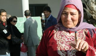 An unidentified Tunisian woman shows ink on her finger after voting in the al-Aouina suburb north of Tunis. Tunisians voted Sunday in their first truly free elections, the culmination of a popular uprising. (Associated Press)