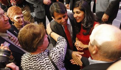 Louisiana Gov. Bobby Jindal, joined by his wife, Supriya, celebrates with supporters at the Renaissance Hotel in Baton Rouge on Saturday after winning re-election. The 40-year-old Republican received about 66 percent of the vote. (Times-Picayune via Associated Press)