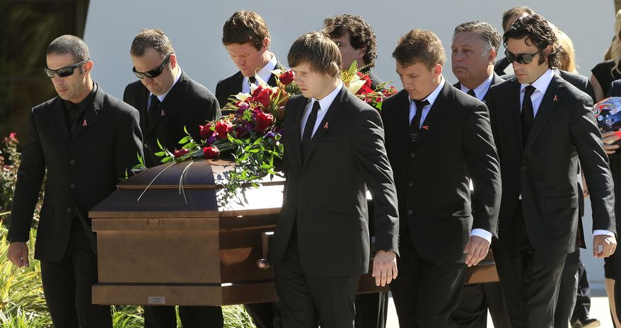 IndyCar drivers Tony Kanaan, left, of Brazil, Scott Dixon, of New Zealand, third from left, and Dario Franchitti, of Scotland, right, carry the coffin of fellow driver Dan Wheldon after funeral services Saturday, Oct 22, 2011, in St. Petersburg, Fla. Wheldon was killed Sunday, Oct. 16, 2011, in a fiery 15-car crash at the Las Vegas Motor Speedway. (AP Photo/Chris O'Meara)