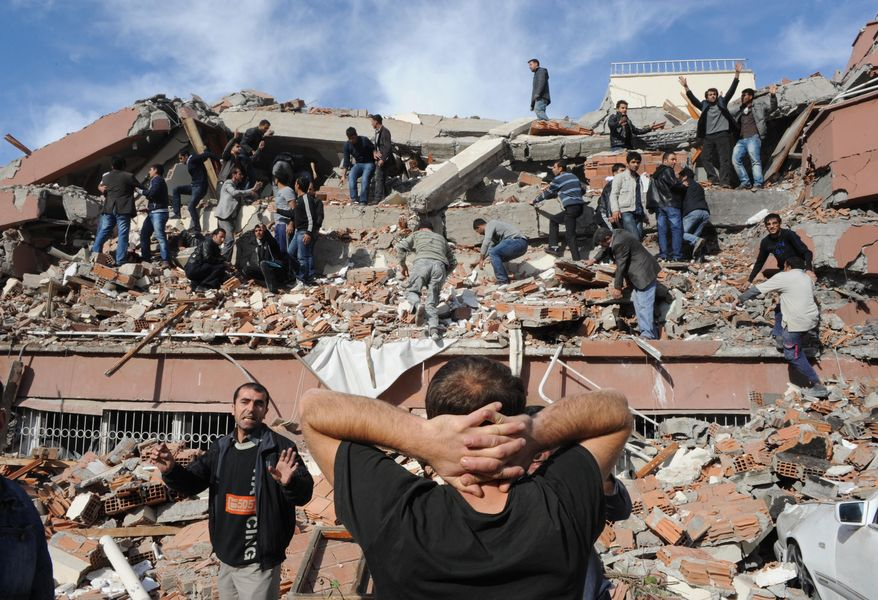 Rescuers look for people trapped under debris in Tabanli village near the city of Van after a powerful earthquake struck eastern Turkey on Sunday, Oct. 23, 2011. (AP Photo/Anatolia, Abdurrahman Antakyali)