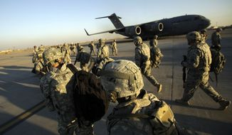 **FILE** Members of the 1st Brigade, 3rd Infantry Division, based at Fort Stewart, Ga., head toward a C-17 aircraft at Sather Air Base in Baghdad in November 2010 as they begin their journey home after a year in Iraq. (Associated Press/Maya Alleruzzo)