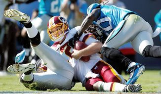 Washington Redskins' John Beck, center, is sacked by Carolina Panthers' Charles Godfrey, right, and James Anderson, left, during the third quarter of an NFL football game in Charlotte, N.C., Sunday, Oct. 23, 2011. (AP Photo/Bob Leverone)