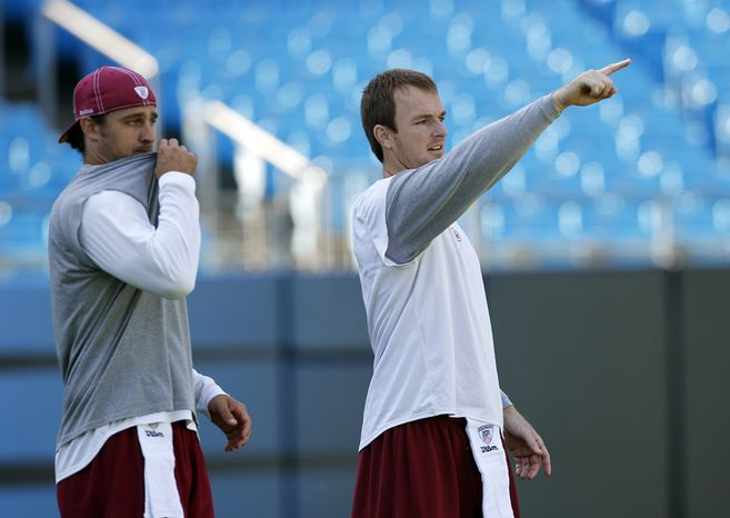 Washington Redskins' John Beck, right, and  Rex Grossman, left, warm up before an NFL football game against the Carolina Panthers in Charlotte, N.C., Sunday, Oct. 23, 2011. (AP Photo/Chuck Burton)