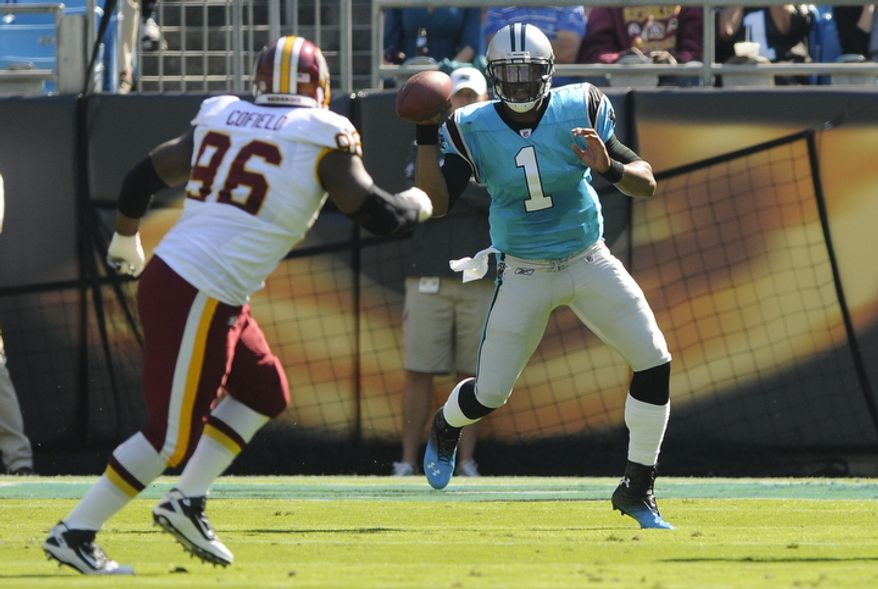 Carolina Panthers' Cam Newton (1) scrambles as Washington Redskins' Barry Cofield (96) pursues during the first quarter of an NFL football game in Charlotte, N.C., Sunday, Oct. 23, 2011. (AP Photo/Mike McCarn)