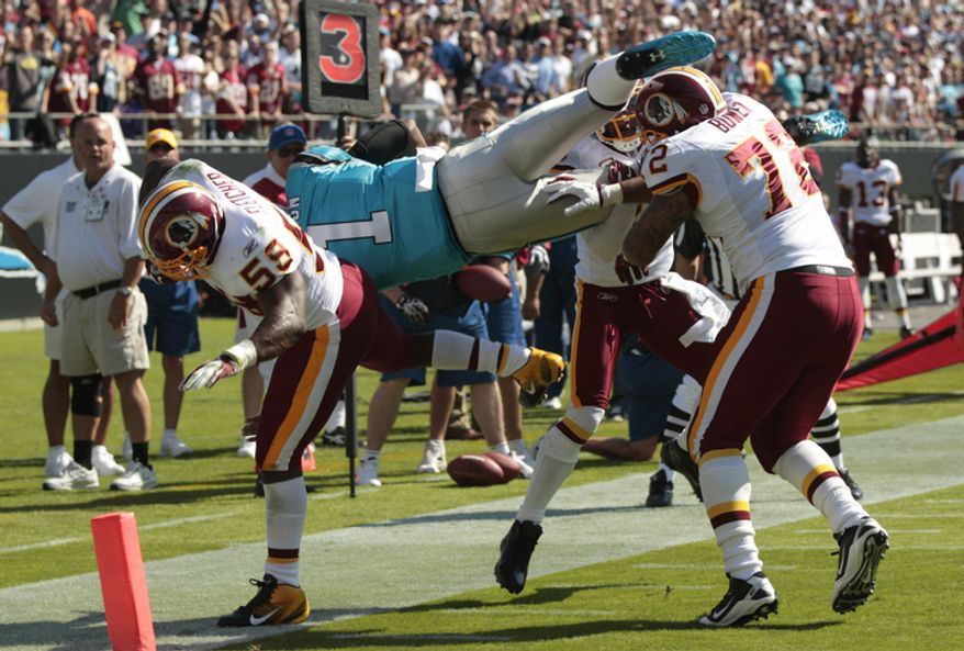 Carolina Panthers' Cam Newton (1) is hit  by Washington Redskins' London Fletcher (59) and Stephen Bowen (72) as he dives for the end zone during the first quarter of an NFL football game in Charlotte, N.C., Sunday, Oct. 23, 2011. (AP Photo/Chuck Burton)