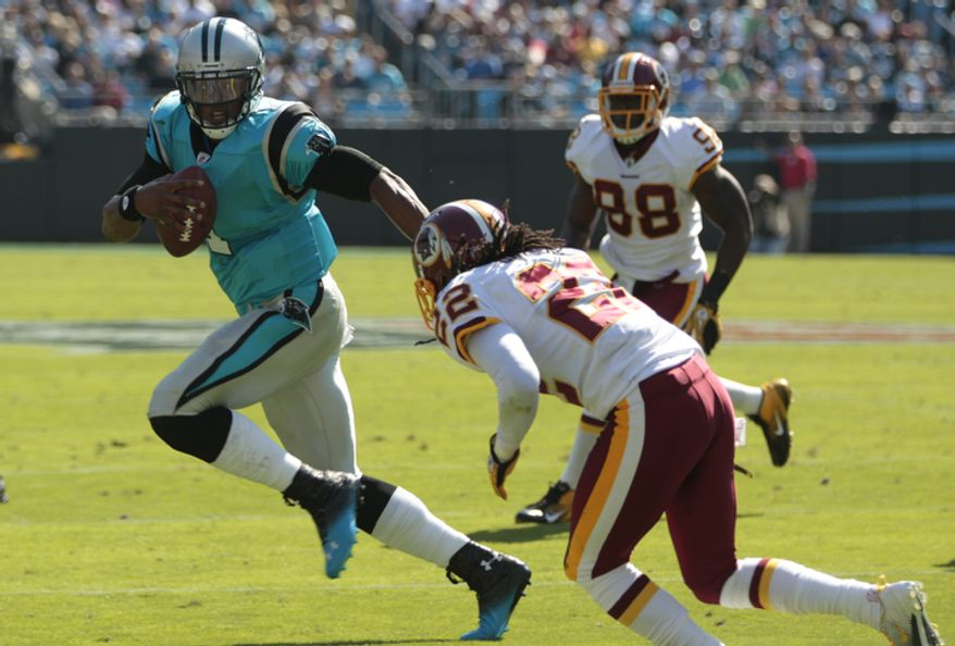 Carolina Panthers' Cam Newton (1) scrambles as Washington Redskins' Kevin Barnes (22) defends during the first quarter of an NFL football game in Charlotte, N.C., Sunday, Oct. 23, 2011. (AP Photo/Chuck Burton)