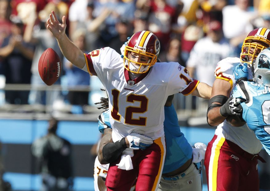 Washington Redskins' John Beck (12) loses the ball as he is hit by a Carolina Panthers player during the first quarter of an NFL football game in Charlotte, N.C., Sunday, Oct. 23, 2011. The Panthers recovered the ball. (AP Photo/Bob Leverone)
