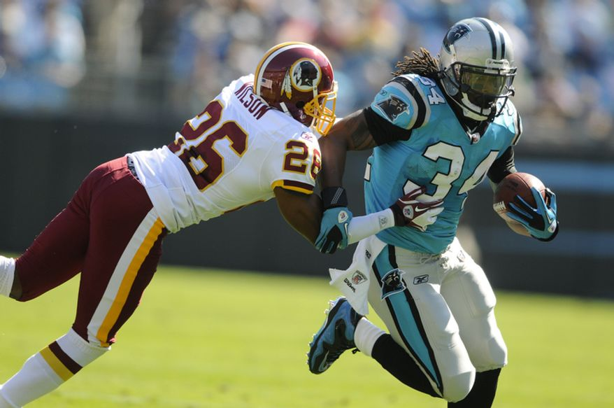 Carolina Panthers' DeAngelo Williams (34) runs as Washington Redskins' Josh Wilson (26) defends during the first quarter of an NFL football game in Charlotte, N.C., Sunday, Oct. 23, 2011. (AP Photo/Mike McCarn)