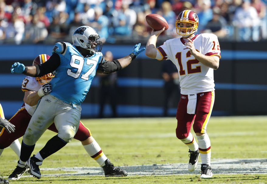 Washington Redskins' John Beck (12) throws a pass under pressure from Carolina Panthers' Terrell McClain (97) during the second quarter of an NFL football game in Charlotte, N.C., Sunday, Oct. 23, 2011. (AP Photo/Chuck Burton)