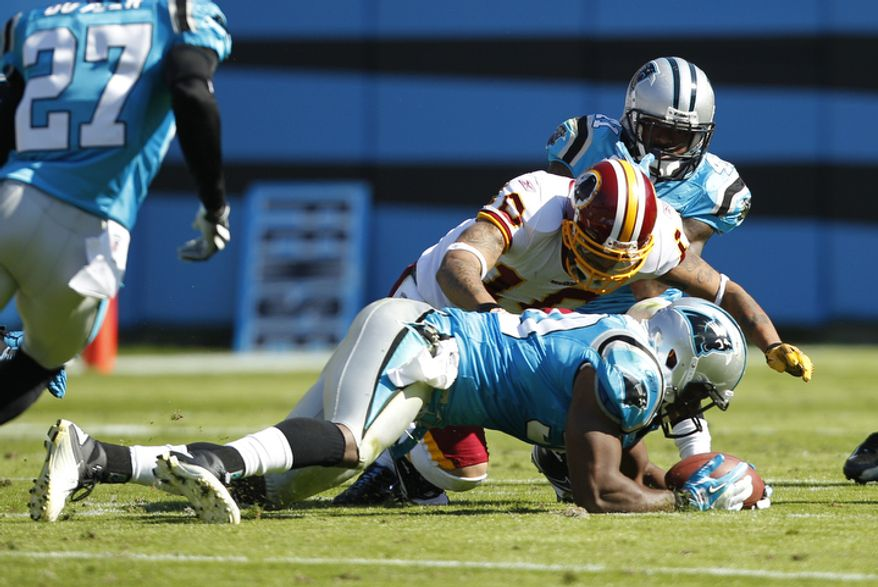 Carolina Panthers' James Anderson, front, recovers a fumble by Washington Redskins' Jabar Gaffney, back, during the second quarter of an NFL football game in Charlotte, N.C., Sunday, Oct. 23, 2011. (AP Photo/Chuck Burton)