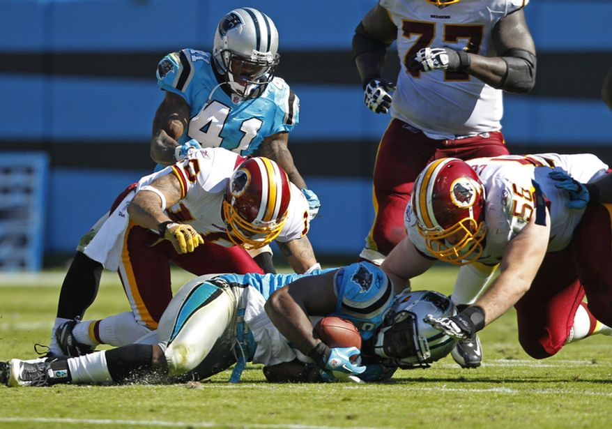 Carolina Panthers' James Anderson, center, recovers a fumble by Washington Redskins' Jabar Gaffney, left, as Redskins' Erik Cook, right, dives in during the second quarter of an NFL football game in Charlotte, N.C., Sunday, Oct. 23, 2011. (AP Photo/Chuck Burton)