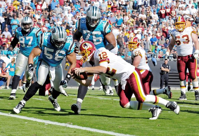 Washington Redskins' John Beck (12) dives into the end zone for a touchdown as Carolina Panthers' Thomas Williams (56) and Greg Hardy (76) defend during the third quarter of an NFL football game in Charlotte, N.C., Sunday, Oct. 23, 2011. (AP Photo/Mike McCarn)