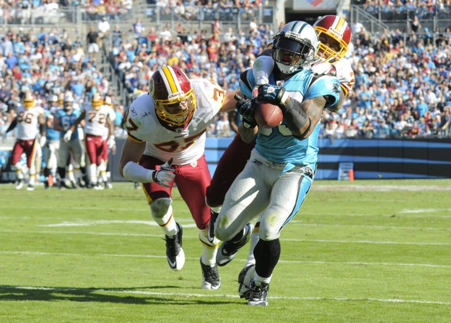 Carolina Panthers' Steve Smith (89) catches a pass as Washington Redskins' Reed Doughty (37) and Josh Wilson (26)  defend during the fourth quarter of the Panthers' 33-20 win in an NFL football game in Charlotte, N.C., Sunday, Oct. 23, 2011. (AP Photo/Mike McCarn)