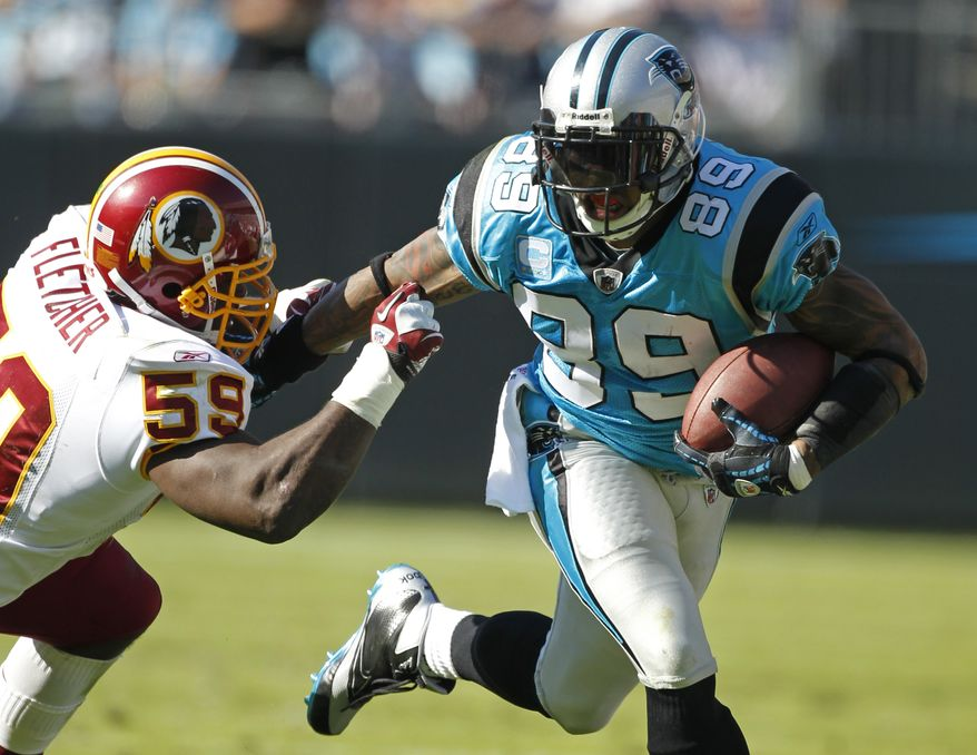 Carolina Panthers' Steve Smith runs the ball as Washington Redskins' London Fletcher pursues during the third quarter of an NFL football game in Charlotte, N.C. on Sunday, Oct. 23, 2011. (AP Photo/Bob Leverone)