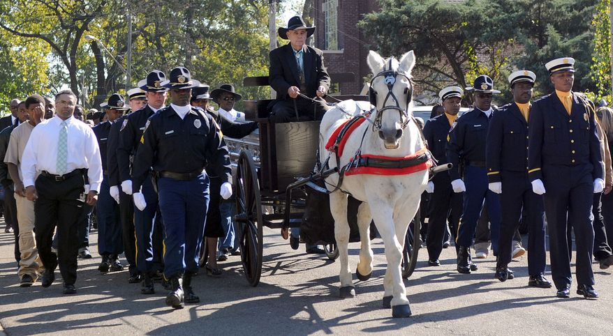Members of the Birmingham Police Department and Birmingham Fire and Rescue escort the casket of the Rev. Fred L. Shuttlesworth from Bethel Baptist Church to the new Bethel Baptist Church in the Collegeville neighborhood of Birmingham, Ala., on Saturday, Oct. 22, 2011. (AP Photo/The Birmingham News, Michelle Campbell)