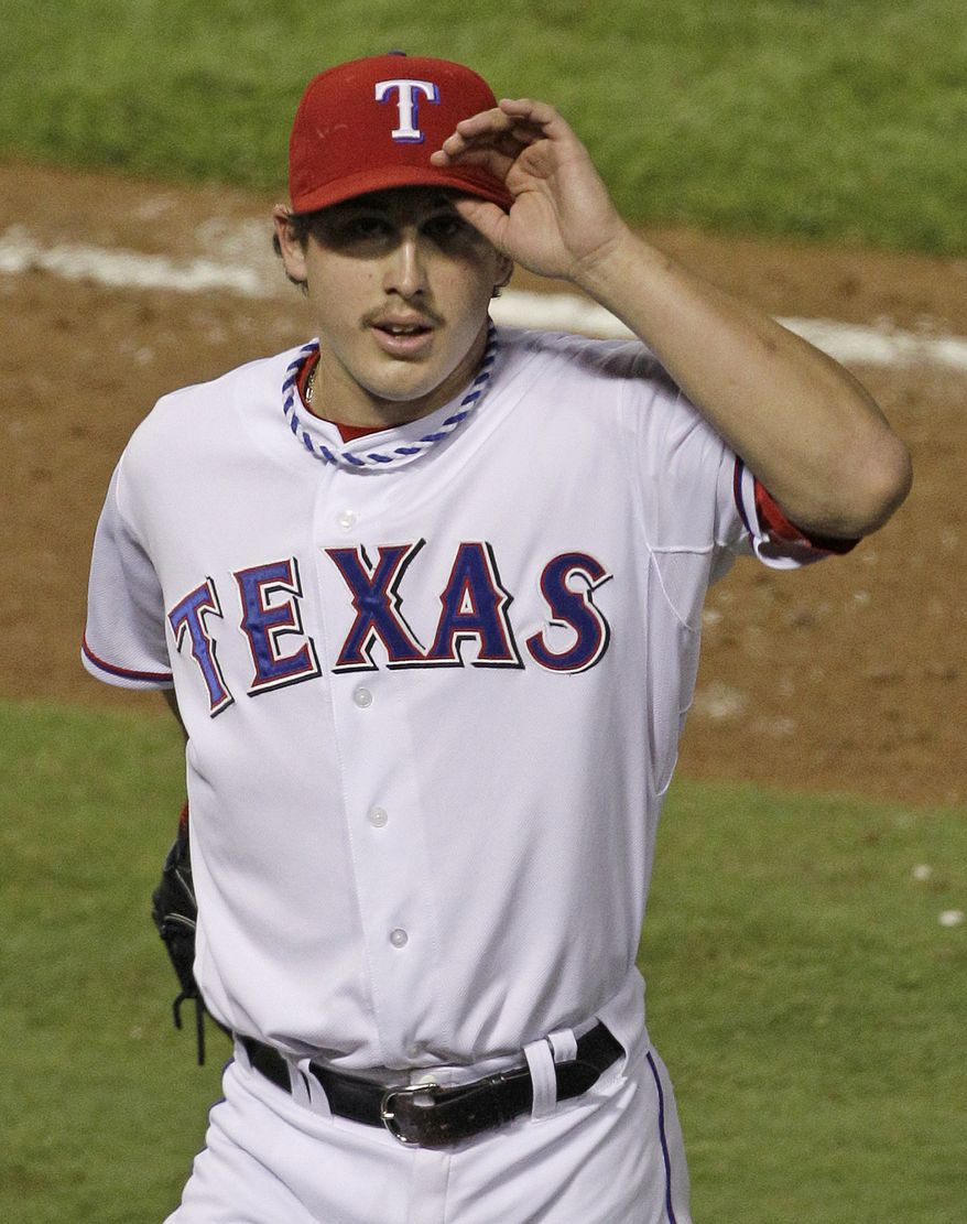 Texas Rangers starting pitcher Derek Holland acknowledges the crowd after he was taken out of the game during the ninth inning of Game 4 of the World Series against the St. Louis Cardinals on Sunday, Oct. 23, 2011, in Arlington, Texas (AP Photo/Paul Sancya)