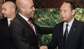 "Haiti's President Michel Martelly (center) shakes hands with former dictator Jean-Claude Duvalier in Port-au-Prince on Oct. 12 with Mr. Duvalier's son, Francois Nicolas ""Nico"" Duvalier, present (left). Mr. Martelly has not sought prosecution of the former dictator, who has been accused of looting the treasury and torturing and killing political opponents. (Associated Press)"