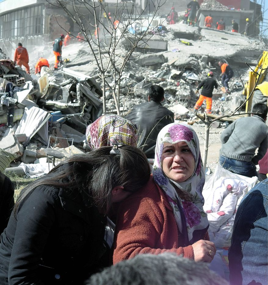 Women wait as rescuers work to save people from debris of their collapsed buildings in Ercis, eastern Turkey, Monday, Oct. 24, 2011. More than 200 people were killed after a powerful quake struck in eastern Turkey with dozens of people are still trapped in debris, but authorities hope the death toll may not rise as high as initially feared. (AP Photo/Burhan Ozbilici)