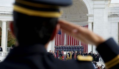1st. Lt. Raziel Amar (top), a chaplain with the New York Army National Guard, salutes during the singing of the National Anthem during Monday's dedication of the Jewish Chaplains Memorial (above) at Arlington National Cemetery. (Rod Lamkey Jr./The Washington Times)