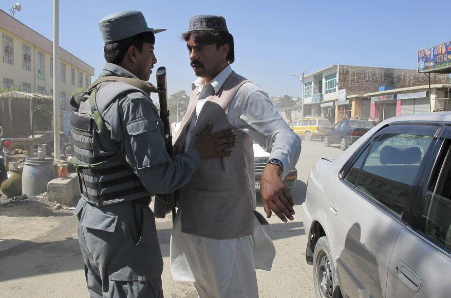 ** FILE ** An Afghan policeman body-checks a man in Khost, Afghanistan, on Sunday, Oct. 2, 2011, after security measures were tightened following the capture of Haji Mali Khan, a senior Haqqani leader inside Afghanistan. (AP Photo/Nishanuddin Khan)