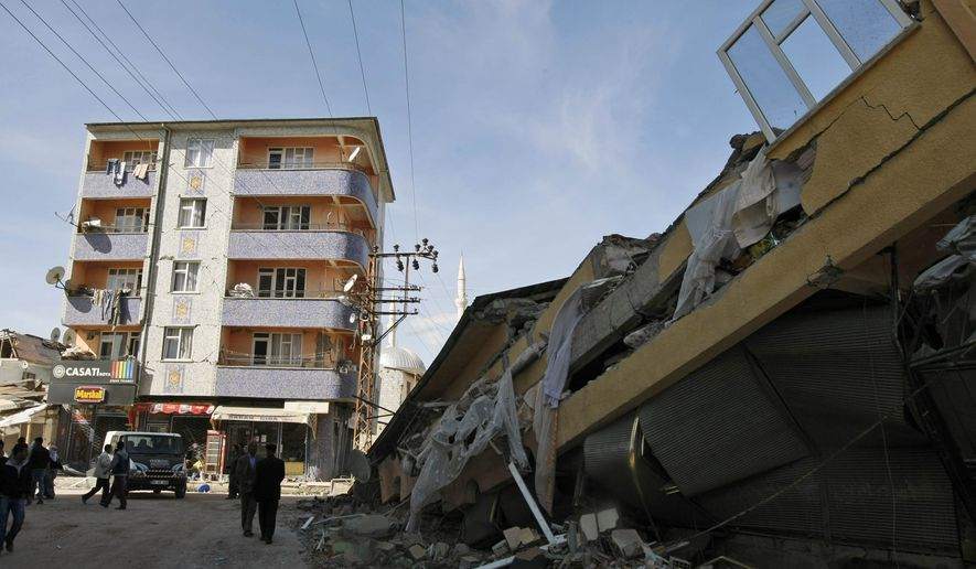 People walk by the debris of collapsed buildings in Ercis, Turkey, on Monday, Oct. 24, 2011, after a 7.2-magnitude earthquake the day before. (AP Photo/Burhan Ozbilici)