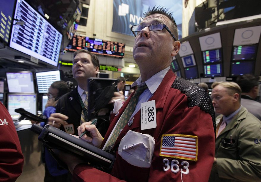 Trader Walter Lundon (second from right) works on the floor of the New York Stock Exchange on Oct. 24, 2011. (Associated Press)