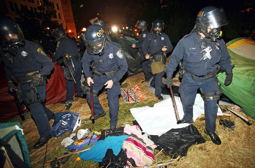 Oakland, Calif., police search tents in Frank Ogawa Plaza as they disperse Occupy Oakland protesters early Tuesday. City officials had been supportive, but later said the protesters were breaking the law and could not stay in the park overnight. (Associated Press)