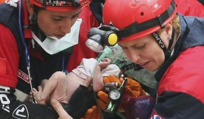 Turkish rescuers carry Azra Karaduman, a 2-week-old baby girl they have saved from under debris of a collapsed building in Ercis, Van, eastern Turkey, Tuesday, Oct. 25, 2011. The baby's mother, Semiha, was still alive, pinned next to a sofa. (AP Photo)