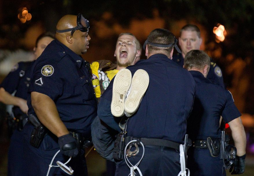 A protester at the Occupy Atlanta demonstration in Woodruff Park is arrested after refusing to leave on Wednesday after Mayor Kasim Reed revoked his executive order allowing the protesters to camp out. (Associated Press)