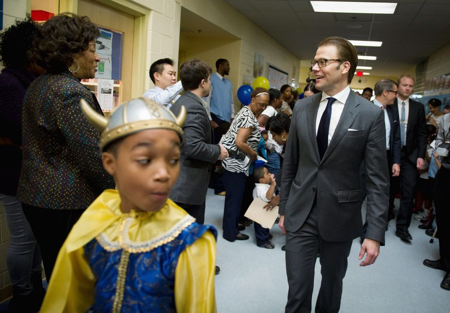 Miner Elementary School fifth-grader Keith Herbert, 10, (above) leads the way for Prince Daniel of Sweden during his visit Wednesday, complete with Swedish flags, for Nordic Food Day. London Gray, 5, tries some of the lunch specialties that included salmon with dill sauce and vinegar-soaked cucumbers. (Rod Lamkey Jr./The Washington Times)