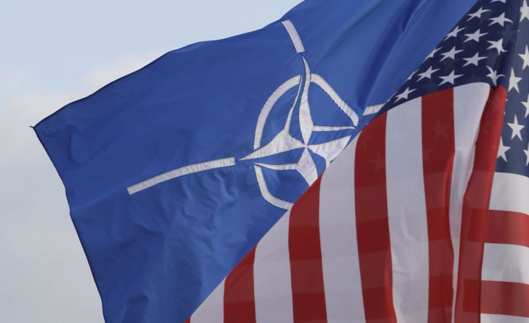 NATO and U.S. flags wave in the breeze outside NATO headquarters in Brussels on Friday, Oct. 21, 2011. (AP Photo/Virginia Mayo)