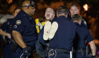 A protestor of the Occupy Atlanta demonstration is arrested after refusing to leave after Mayor Kasim Reed revoked his executive order allowing the protestors to camp out in Woodruff Park early Wednesday, Oct. 26, 2011, in Atlanta. (AP Photo/David Goldman)