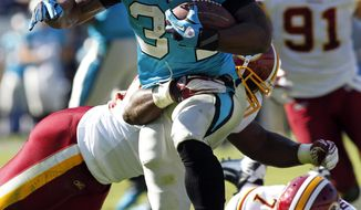 Carolina Panthers' DeAngelo Williams (34) slips through the grasp of Washington Redskins' London Fletcher, Stephen Bowen and Josh Wilson during an NFL football game in Charlotte, N.C., Sunday, Oct. 23, 2011. The Carolina Panthers beat the Washington Redskins 33-20. (AP Photo/Bob Leverone)