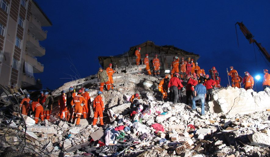 Rescuers work around the clock under floodlights in hopes of finding more people alive in the rubble of a pancaked building in Ercis, Turkey, on Tuesday, Oct. 25, 2011. (AP Photo/Selcan Hacaoglu)