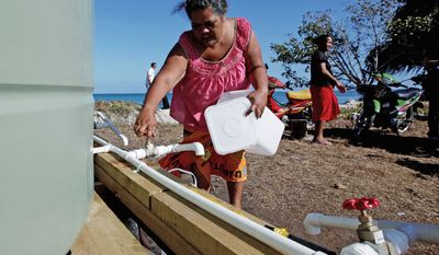 Residents collect their morning ration of fresh water made from desalinated sea water in Funafuti, the capital of Tuvalu. The group of atolls situated north of Fiji and northwest of Samoa are suffering a severe drought and water shortage, coupled with contaminated groundwater due to rising sea levels. (Associated Press)