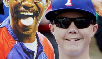Drew Webb holds up picture of Texas Rangers manager Ron Washington before Game 3 of baseball's World Series between the St. Louis Cardinals and the Texas Rangers Saturday, Oct. 22, 2011, in Arlington, Texas. (AP Photo/Paul Sancya)