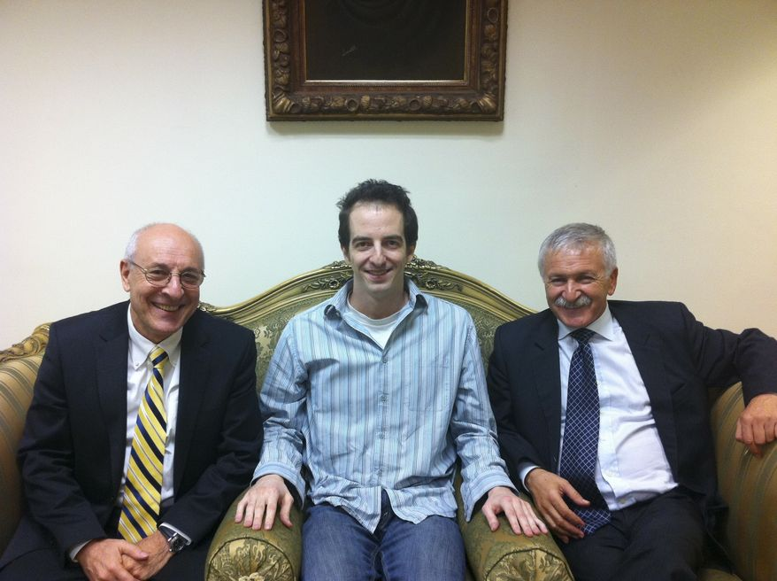 In this photo made available by the office of Israeli Knesset Member Israel Hasson on Wednesday, Oct. 26, 2011, Ilan Grapel, a U.S.-Israeli citizen arrested in Egypt, sits between Israel Hasson, right, and lawyer Yitzhak Molcho, left, in Cairo, Egypt. Israel on Tuesday officially approved a deal to swap 25 Egyptian prisoners for Grapel, who was arrested in Egypt in June 2011 on suspicions of espionage. (AP Photo/MK Israel Hasson Office, HO)