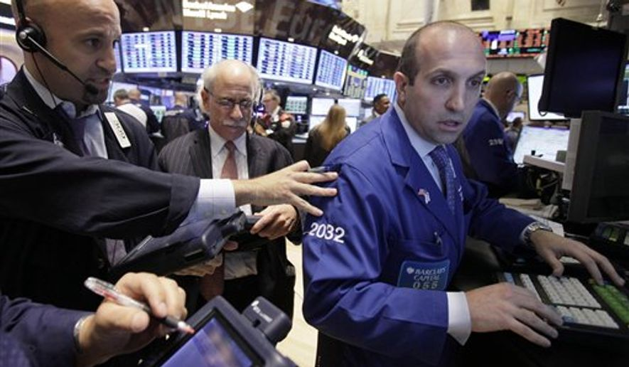 Specialist James Denaro, right, directs trading at his post on the floor of the New York Stock Exchange Thursday, Oct. 27, 2011. (AP Photo/Richard Drew)