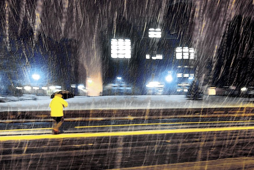 A pedestrian walks in a burst of moderate snow in front of the town hall in Vernon, Conn., on Oct. 27, 2011, during the first snowfall of the season. (Associated Press/Journal Inquirer, Jim Michaud)