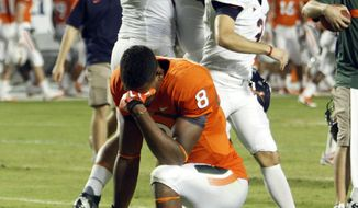 Virginia's Brent Urban (99) and Sean Cascarano, upper right, celebrate their 28-21 win as Miami's Tommy Streeter (8) reacts following an NCAA college football game in Miami, Thursday, Oct. 27, 2011. (AP Photo/Alan Diaz)