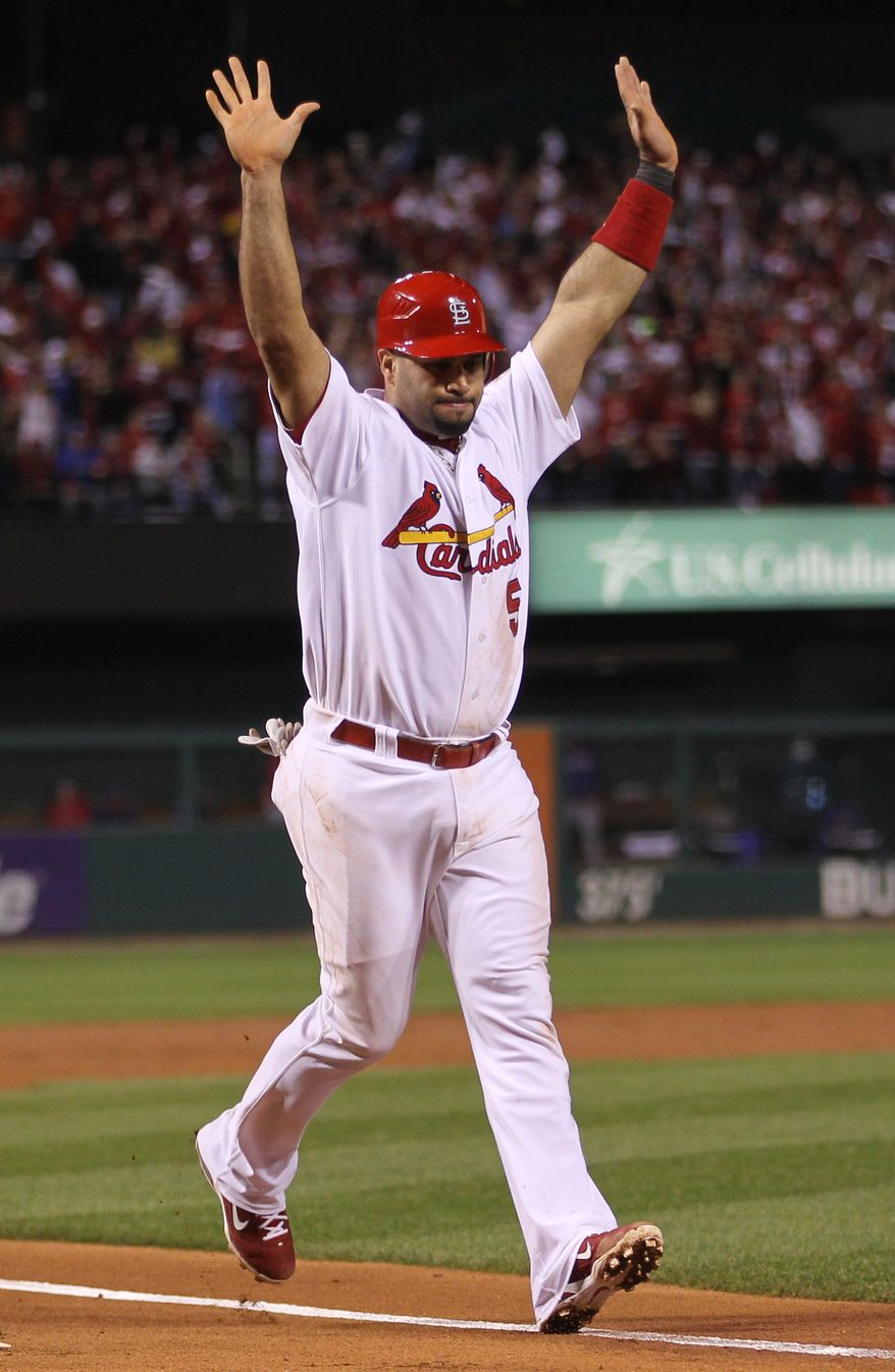 Albert Pujols of the St. Louis Cardinals reacts as he scores during the first inning of Game 7 of baseball's World Series against the Texas Rangers on Friday, Oct. 28, 2011, in St. Louis. (AP Photo/Ezra Shaw, Pool)