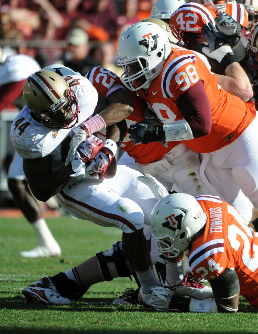 Virginia Tech defenders Derrick Hopkins (98), Tariq Edwards (24) stop Boston College running back Andre Williams (44) during the first half at Lane Stadium, Saturday Oct. 22, 2011, in Blacksburg, Va. (AP Photo/Don Petersen)