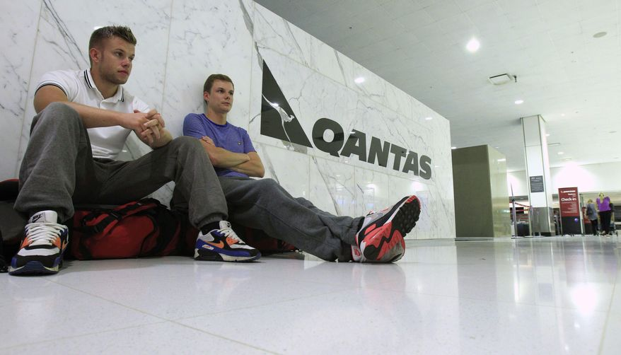 Brothers Kevin and Chris Crulley, sit on the floor at the Qantas check-in counter at Sydney Airport in Sydney, Saturday, Oct. 29, 2011, after they were removed from their flight home to England. (AP Photo/Rick Rycroft)