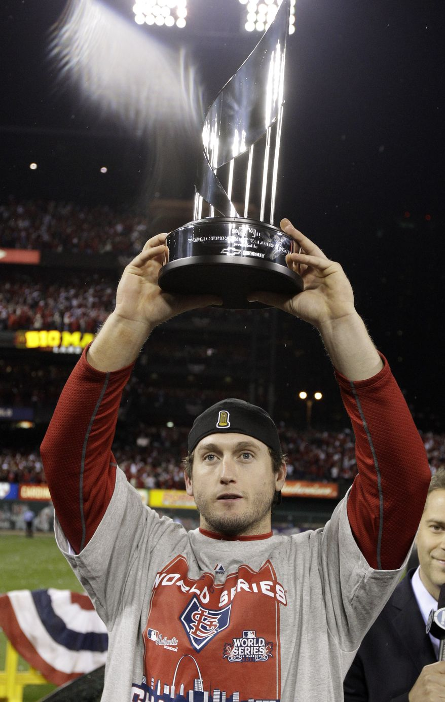St. Louis Cardinals' David Freese holds up the MVP trophy after Game 7 of baseball's World Series against the Texas Rangers Friday, Oct. 28, 2011, in St. Louis. The Cardinals won 6-2 to win the series. (AP Photo/Charlie Riedel)