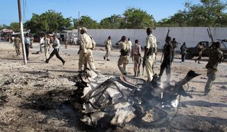 Somali soldiers patrol near a car-bombing site in Mogadishu, Somalia. The bomb exploded near Somalia's Foreign Ministry on Tuesday, killing at least four people including the bomber. (Associated Press)