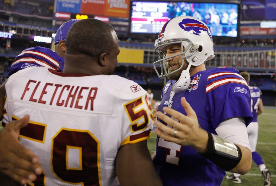 Buffalo Bills' Ryan Fitzpatrick (14) greets Washington Redskins' London Fletcher (59) after an NFL football game at the Rogers Centre in Toronto, Sunday, Oct. 30, 2011. The Bills won 23-0.(AP Photo/Gary Wiepert)