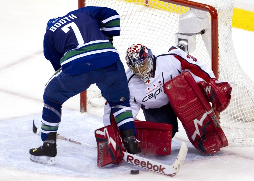 Vancouver Canucks left wing David Booth tries to get a shot past Washington Capitals goalie Michal Neuvirth in Vancouver, British Columbia, (AP Photo/The Canadian Press, Jonathan Hayward)