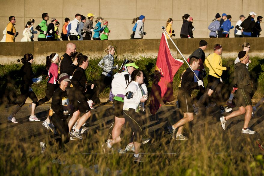 A runner carries a Marine Corps flag as the race breaks in to a spot of sun during the 36th Marine Corps Marathon in Arlington, Va. on Oct. 30, 2011.(T.J. Kirkpatrick/ The Washington Times)
